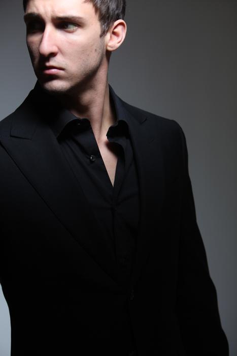 szofisztikált viselet a fekete öltöny fekete kigombolt magas galléros inggel